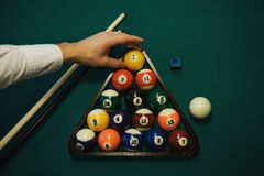 Playing billiard. Billiards balls and cue on green billiards table. Caucasian player put yellow ball inside. View from up. Billiard sport concept. Pool Stock Photography