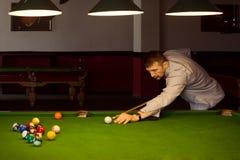 Playing in billiard club. The pool gamer is playing snooker in billiard club indoors stock images
