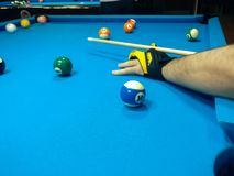 Playing billiard, A shot of a man playing billiard on a blue pool table stock photo