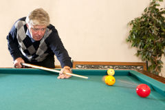 Playing billiards. Senior man playing a game of carambole billiards - selective focus on the billiard balls Stock Images