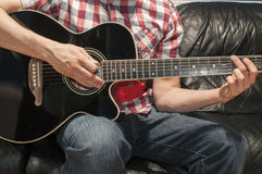 Playing a black acoustic guitar. Man playing music on an acoustic guitar on a couch Royalty Free Stock Photos