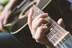 Playing black classic guitar close up on fretboard and hands Stock Photography