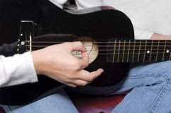 Playing a Black Guitar Royalty Free Stock Images