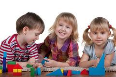 Playing blocks on the floor. Three lying on the carpet children are playing blocks; isolated on the white background Royalty Free Stock Photos
