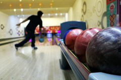 Playing bowling. Man playing bowling in club stock photos