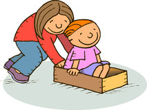 Playing with a box. Girl pushing a boy that is seated inside a box Royalty Free Stock Photos
