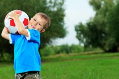 Playing boy. Shot of a cute laughing boy with a ball outdoor Stock Photo