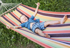 Playing boy in striped hammock Royalty Free Stock Images