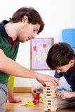 Playing with boys' toys. Son and dad playing building a tower of blocks Royalty Free Stock Photography