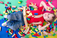 Playing with bricks. Little boy is surrounded by many blocks Stock Image