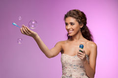 Playing with a bubble wand. Beautiful young women playing with t Royalty Free Stock Photography