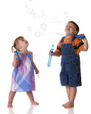 Playing Bubbles. A brarefoot preschool boy blowing bubbles for his little sister.  Isolated on white Royalty Free Stock Photography