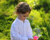 Playing with bubbles. Small boy playing with soap bubbles in the garden Stock Photo