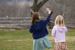 Playing bubbles. Two young girls play wtith bubbles Royalty Free Stock Photo