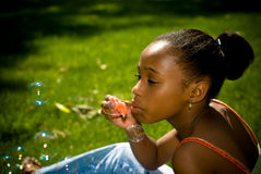 Playing With Bubbles. A young african american girl blowing bubbles in the spring outdoors Royalty Free Stock Images