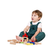 Playing with building blocks. Little cute boy playing with building blocks. Isolated on white stock images
