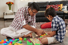 Playing building blocks. Father and son playing building blocks together royalty free stock photo