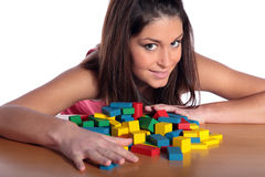 Playing with building bricks. An attractive young woman playing with building bricks. All isolated on white background royalty free stock photography