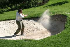 Playing from the bunker. To the green stock image