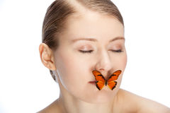 Playing with butterfly. Butterfly covering mouth of a young womans face Royalty Free Stock Photography