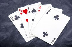 Five playing card`s stud hand three of a kind six and ace a two fun Stock Photo