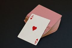 Playing card with red heart as original stylized greeting card for Valentine`s Day on deck of cards on black background. royalty free stock images
