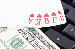 Playing card and US dollar on the computer keyboard Stock Image