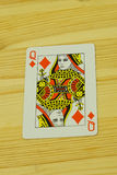 A playing card on a wooden desk Stock Images