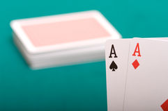 Playing cards. Two ases close up against a pack on green cloth Stock Image