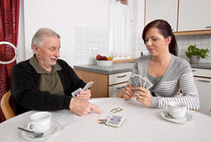 Playing cards. A young woman plays with seniors in their free time with playing cards Royalty Free Stock Photo