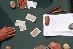 Playing cards. People playing cards in a green table Stock Images