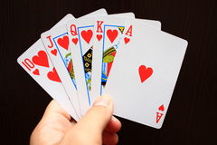 Playing cards. A hand holding heart royal straight flush, against black table background