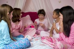 Playing Cards. Five adorable girls at a slumber party playing cards stock photo