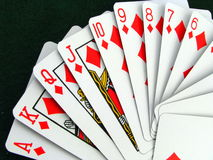 Playing Cards. A fan of red diamond playing cards on a green felt background royalty free stock images