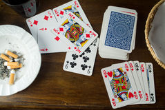 Playing cards and ash tray on a table. Playing cards and ash tray full of butt on a brown table Royalty Free Stock Photography