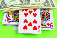 Playing cards and cash on green table Royalty Free Stock Photos
