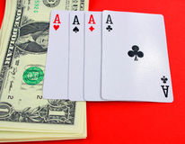 Playing cards and cash on red table Stock Images