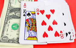 Playing cards and cash on red table Stock Photo