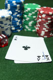 Playing cards Clubs Dice Poker chips. Stacks of gambling chips and dice in the background and a pair of cards Ace and King of Clubs on green baize table top Stock Photos