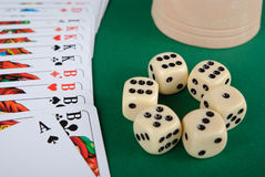 Playing cards, dices and cup on green background stock photography