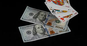 Playing cards falling on Dollar Banknotes against Black Background, stock video footage