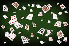 Playing cards flying at the poker table Stock Photos