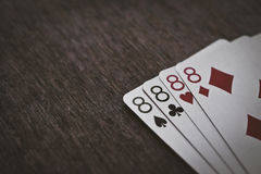 Playing cards four eights closeup on a wooden table. Space for text. copyspace Stock Photo