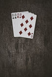 Playing cards four eights on a wooden table. Space for text. v Stock Image