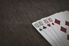 Playing cards. Four tens on a wooden table closeup. abstraction background and gambling. Space for text Stock Image