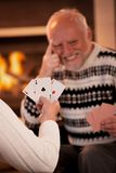 Playing cards in front of fireplace. Senior man laughing in background, focus on female hand holding winning cards, three ace Royalty Free Stock Photos