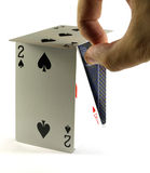 Playing cards game. Playing cards doing a litle house and a hand ready to knock it down royalty free stock photo