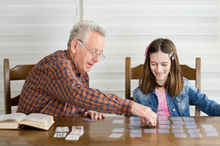 Playing cards. Grandpa and granddaughter playing memory game with cards Royalty Free Stock Images