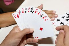 Playing cards in hand. And table Royalty Free Stock Photos