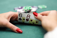 Playing cards in hands. Playing cards and chips in hands. chips on green background Royalty Free Stock Photography